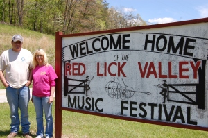 David and his wife Paula with the hand-painted festival sign next to Red Lick Road.